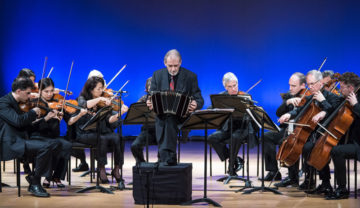 A man plays an accordion in front of an orchestra