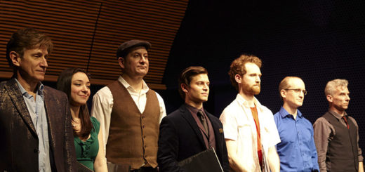 Opera singers stand in a line on stage