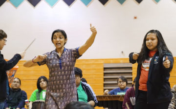 A teacher instructs a student on dance move