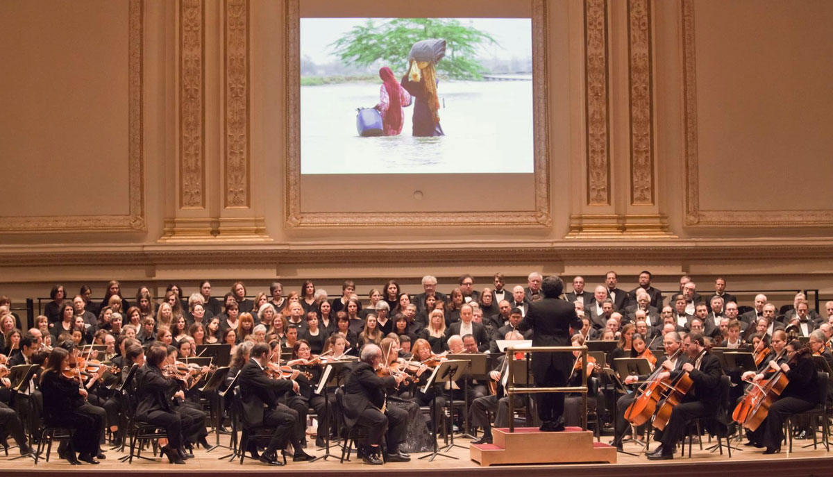An orchestra performs with a photo of flood victims projected on the wall