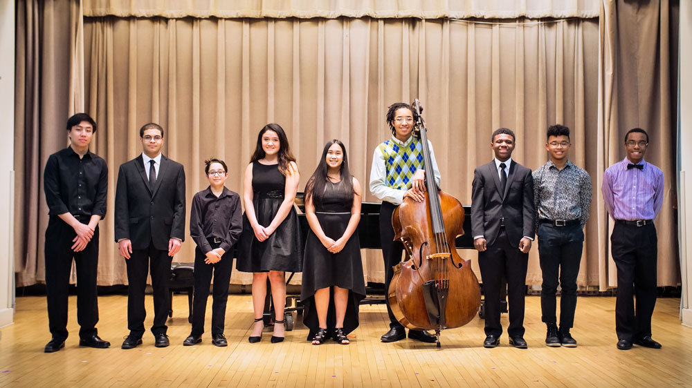 Student musicians stand on stage after a performance