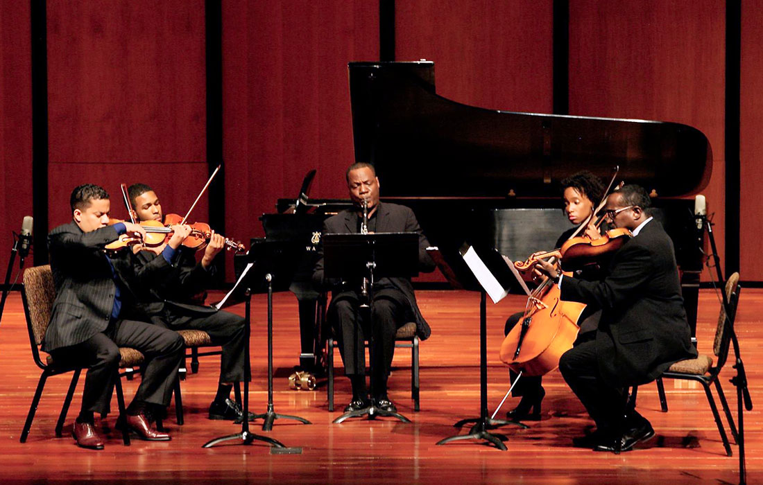 A chamber orchestra performs on stage