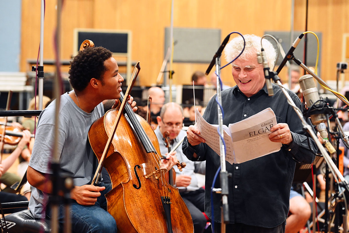 Sheku Kanneh holds a cello and laughs with a conductor