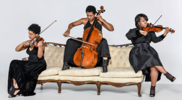 Three musicians play on different parts of an antique couch